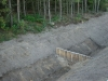 Próg przegrody wykonany z palisady z kołków drewnianych, przed ułożeniem geowłókniny