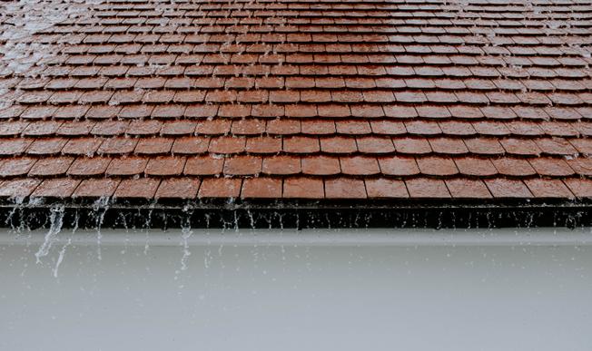 Zdjęcie 2. Zdjęcie deszczu padającego na dach. Dla dachów szczelnych, w zależności od spadku powierzchni, współczynnik spływu wynosi od 0,85 do 1,0. Źródło: canva.com Autor: Adrien Olichon.